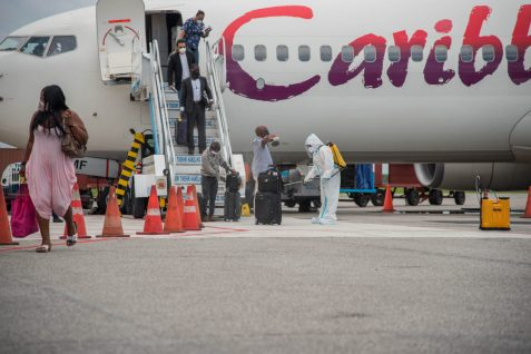 Passenger being sanitized as the disembark the Caribbean Airline flight at the Cheddi lagan International Airport