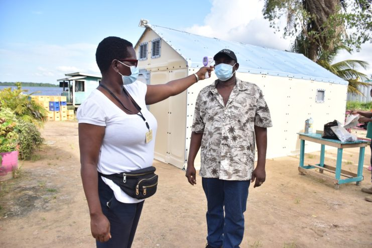 Community Health Worker, Everly Sampsonchecks the temperature of a resident in Buck Hall