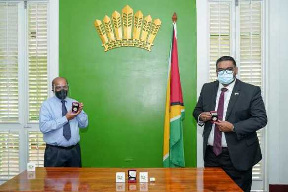 His Excellency, Dr. Irfaan Ali, President of the Cooperative Republic of Guyana, and Dr. Gobin Ganga, Governor of the Bank of Guyana show off the two commemorative coins at State House, this morning