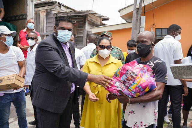 President of the Cooperative Republic of Guyana, His Excellency Dr. Moahmed Irfaan Ali and First Lady Arya Ali present a resident of Tiger Bay with a hamper.