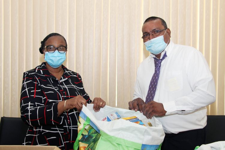 Permanent Secretary, Ministry of Human Services and Social Security, Ms. Lorene Baird, receives the hampers from Mr. Latchman Bharat, a representative of the Church of Jesus Christ of the Latter-Day Saints