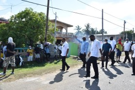 Prime Minister Brigadier Mark Phillips (centre) waves to residents during his visit to Number Three Village, Mahaica-Berbice (Region Five).