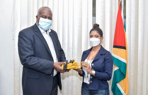 Prime Minister Brigadier Mark Phillips receives a collector's model of a bulldozer from MACORP's Human Resources Manager, Ms. Anita Ramprasad, during a courtesy call the Company paid on him today.