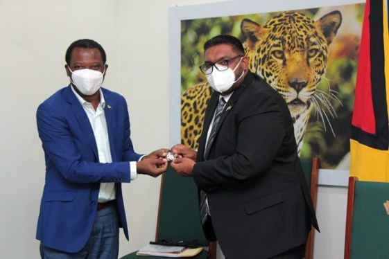 Minister of Foreign Affairs and International Cooperation, the Honourable Hugh Todd present the President of the Co-operative Republic of Guyana, His Excellency Dr. Mohamed Irfaan Ali, with a commemorative G-77 pin