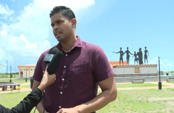 Minister of Culture, Youth and Sport, Hon. Charles Ramson Jr. in front of the Indian Arrival Monument in Palmyra, East Berbice-Corentyne (Region Six)