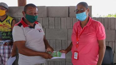 A Region Nine resident receives his cash grant from Lethem Town Councillor Megan Thomas