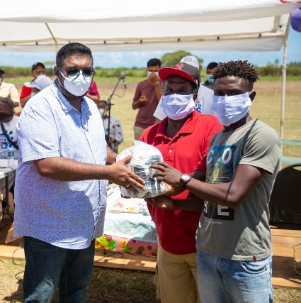 President Dr. Mohamed Irfaan Ali presents a quantity of football gear to these Leguan youth