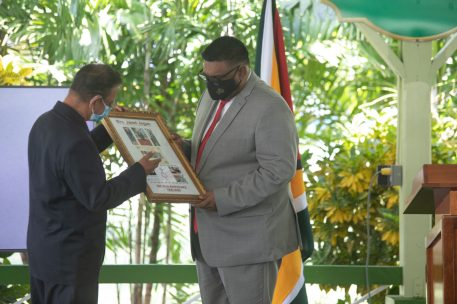 His Excellency Dr. Mohamed Irfaan Ali receives a copy of the commemorative collection honouring late former president Mrs. Janet Jagan from Chairman of the Cheddi Jagan Research Centre, Mr. Hydar Ally