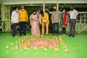 President Dr. Mohamed Irfaan Ali lights a diya as First Lady, Mrs. Arya Ali their son, Zayd; Vice President, Dr. Bharrat Jagdeo; Prime Minister Hon. Brigadier (ret'd) Mark Phillips and Mrs. Mignon Phillips and Ministers Hugh Todd and Oneidge Walrond look on