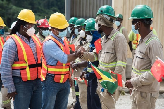 Minister of Natural Resources, Hon. Vickram Bharrat greeting a Guyanese employee at the Aurora Gold Mine. Permanent Secretary at the Ministry, Mr. Joslyn McKenzie is pictured at left.
