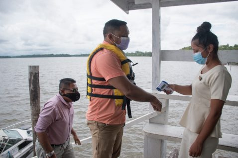 Minister of Natural Resources, Hon. Vickram Bharrat submits himself to a temperature check on his arrival at Orealla. Minister of Agriculture, Hon. Zulfikar Mustapha is following closely behind