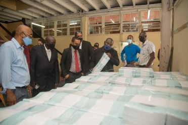 Minister within the Office of the Prime Minister, Hon. Kwame McCoy (third from right) and Directors of the GNNL Board examine some of the documents being printed by the entity.