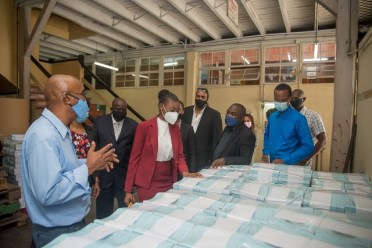 Minister within the Office of the Prime Minister, Hon. Kwame McCoy pays keen attention as this staff at the Guyana National Printers Limited explains how production is done.