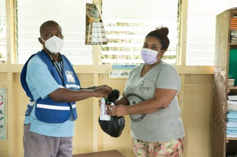CDC's, Owen Paul distributes cleaning supplies to a resident of Great Troolie Island.