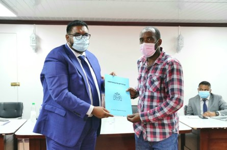 Mr. Essan Garraway receives his land title from President Dr. Mohamed Irfaan Ali.