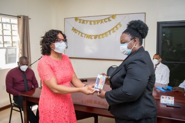 PAHO representative, Ms. Karen Roberts hands over a cellular phone to Director of the Mental Health Unit, Dr. Util Richmond-Thomas.