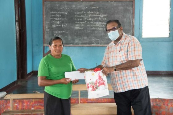 Minister within Ministry of Local Government and Regional Development, Hon. Anand Persaud presents school vouchers to this parent in Rewa Village