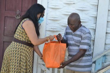 Minister of Human Services and Social Security, Dr. Vindhya Persaud hands over a food hamper to resident Mr. Milton Quealy