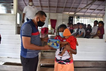 Minister of Housing and Water, Hon. Collin Croal gives this toddler a present in Region One