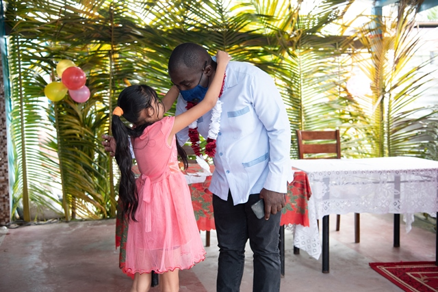 A brave young lady places a garland on Minister within the Office of the Prime Minister, Hon. Kwame McCoy
