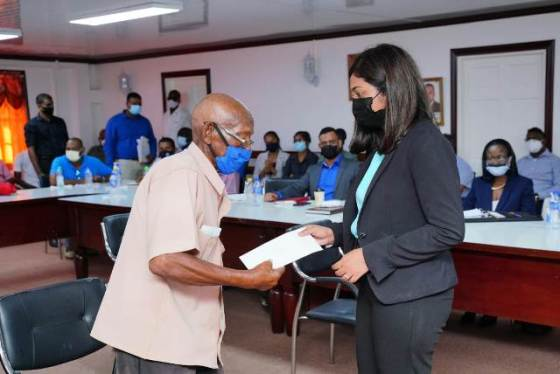 Mr James receiving two months back pay of old age pension from Ms Shannielle Hoosein-Outar, Permanent Secretary of the Ministry of Social Services