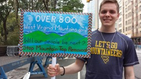 Young man holding a painted sign with text