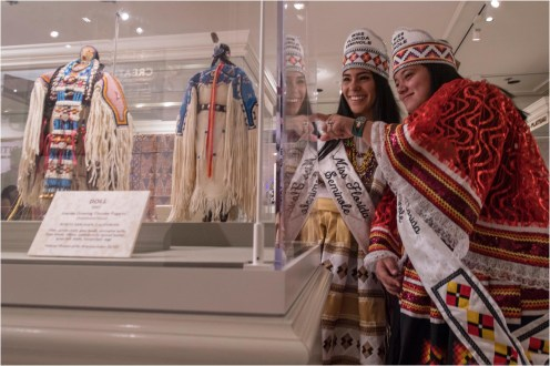 """Miss Florida Seminole, Cheyenne Kippenberger, and Jr. Miss Florida Seminole, Allegra Billie, of the Seminole Tribe, see how intricate American Indian beadwork techniques are passed down through generations while viewing dolls on display in """"Creating Tradition: Innovation and Change in American Indian Art"""" inside The American Adventure pavilion at Epcot at Walt Disney World Resort. The dolls were created by artists Juanita Growing Thunder and her grandmother, Joyce Growing Thunder, with the Assiniboine/Sioux tribes. Both dolls are on loan from the Smithsonian's National Museum of the American Indian. The exhibition showcases the work of contemporary Native artists alongside artifacts from centuries past, demonstrating how ancestral craftsmanship influences modern generations. (Kent Phillips, photographer)"""