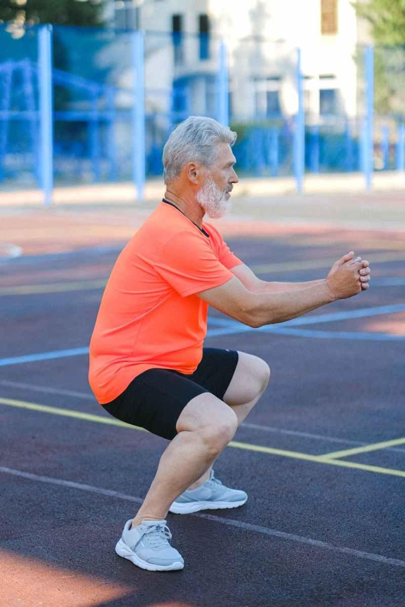 mature sportsman doing exercises on stadium