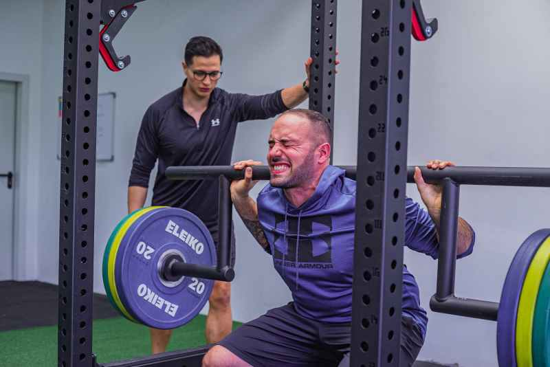 strong man doing weightlifting exercise in gym