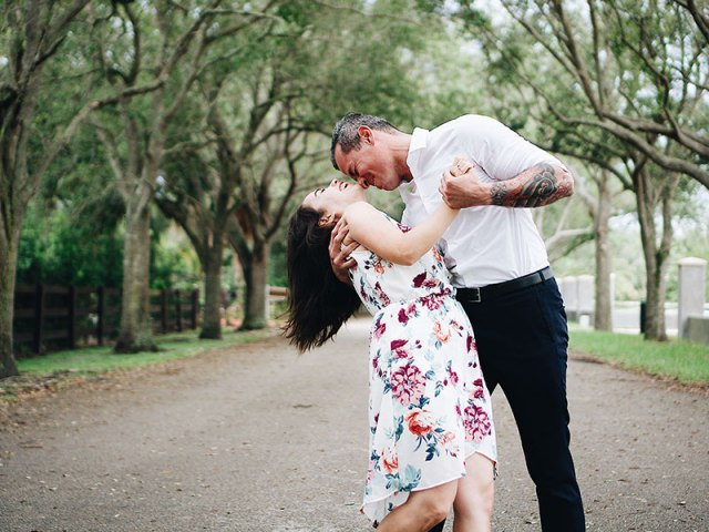 A couple in an older man younger woman relationship dancing under the trees and laughing.