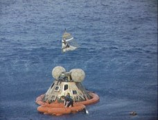 Astronaut John L. Swigert Jr., command module pilot, is lifted aboard a helicopter