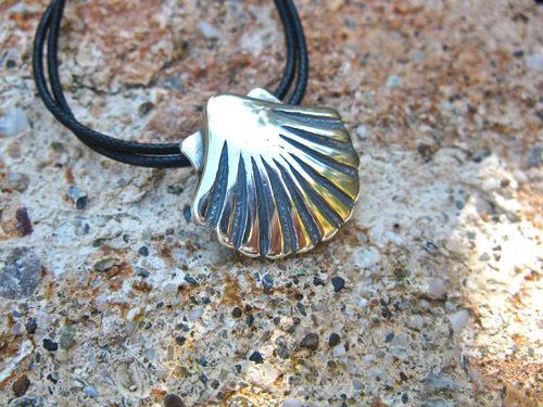 Symbolic silver scallop shell on black double cord