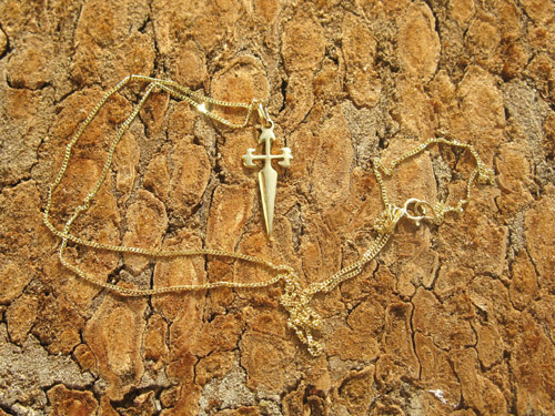 This 18ct gold cross of St James hangs on a fine gold curb chain