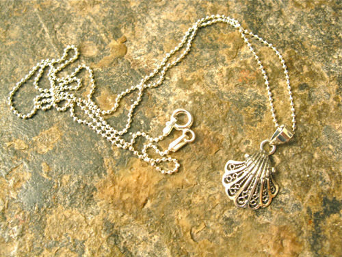 The shell hangs on a sterling silver diamond cut ball chain that sparkles in the light