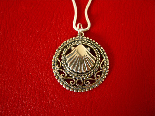 Close-up of the Camino scallop shell surrounded by an ornate filigree border