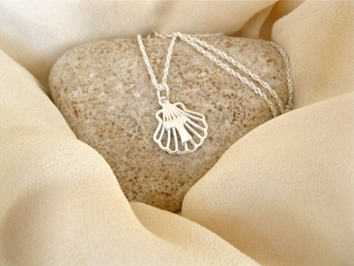 The shell with Tau cross hangs on a pretty rope chain