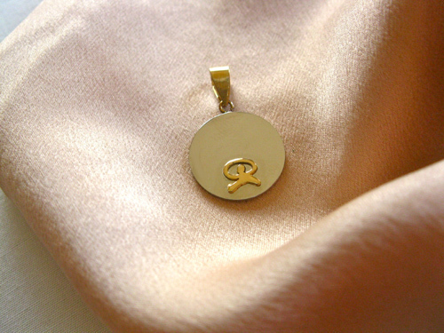 The round pendant is stainless steel and features an 18ct gold Indalo