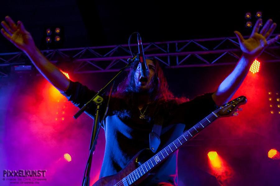 Ein Gitarrist steht auf der Bühne vor einem Mikrofon