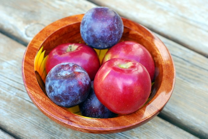 apples and plums in bowl