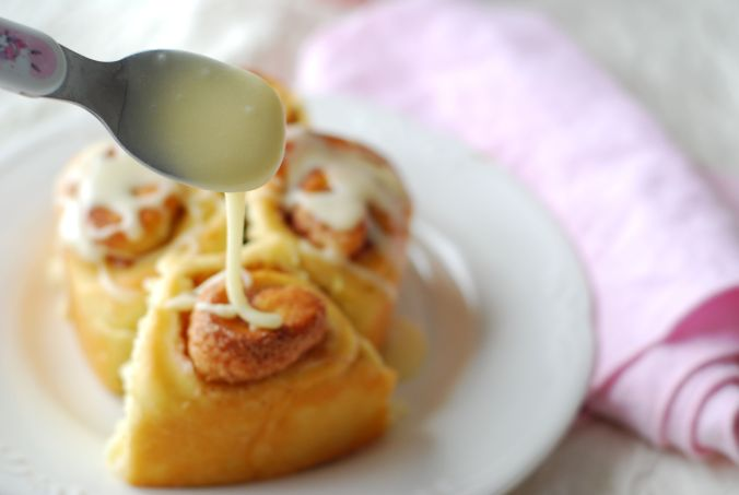 maple frosted cinnamon rolls with spoon