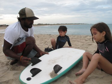 Krishantha Ariyasena teaching Max, 6, and Verity, 9, some theories of surfing while still on the beach at Arugam Bay. Credit: Alex Frew McMillan