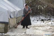 zaatari woman sweeping snow