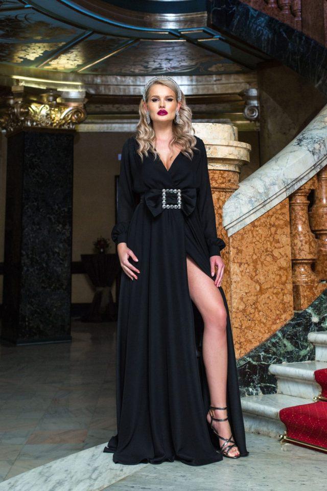 Rochie neagra lunga de ocazie in clos cu decolteu petrecut in v accesorizata cu o catarama si crapata pe picior