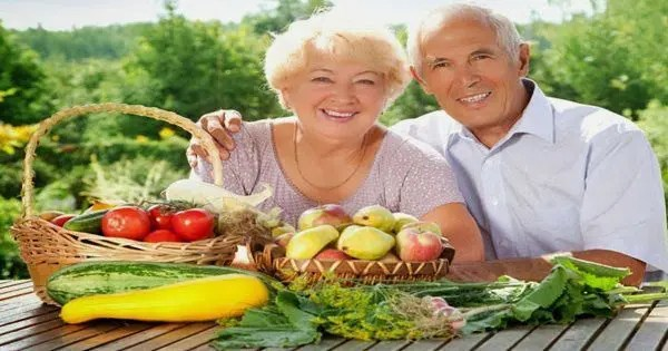 blog picture of elderly couple sitting outside with vegetables