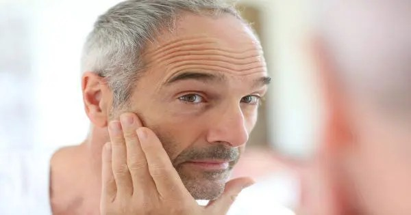 blog picture of older man looking at self in the mirror