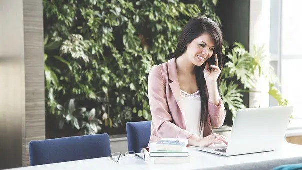 lady at office desk smiling