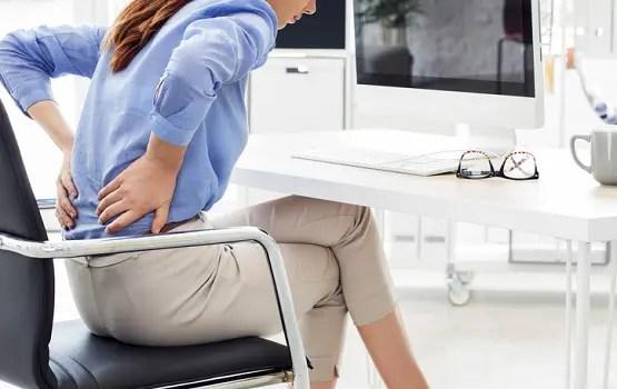 Kobieta trzyma ją z powrotem, gdy doświadcza rwy kulszowej w ustawieniu pracy.