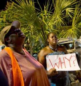 Woman holds a sign, asking why, after the church violence in Charleston
