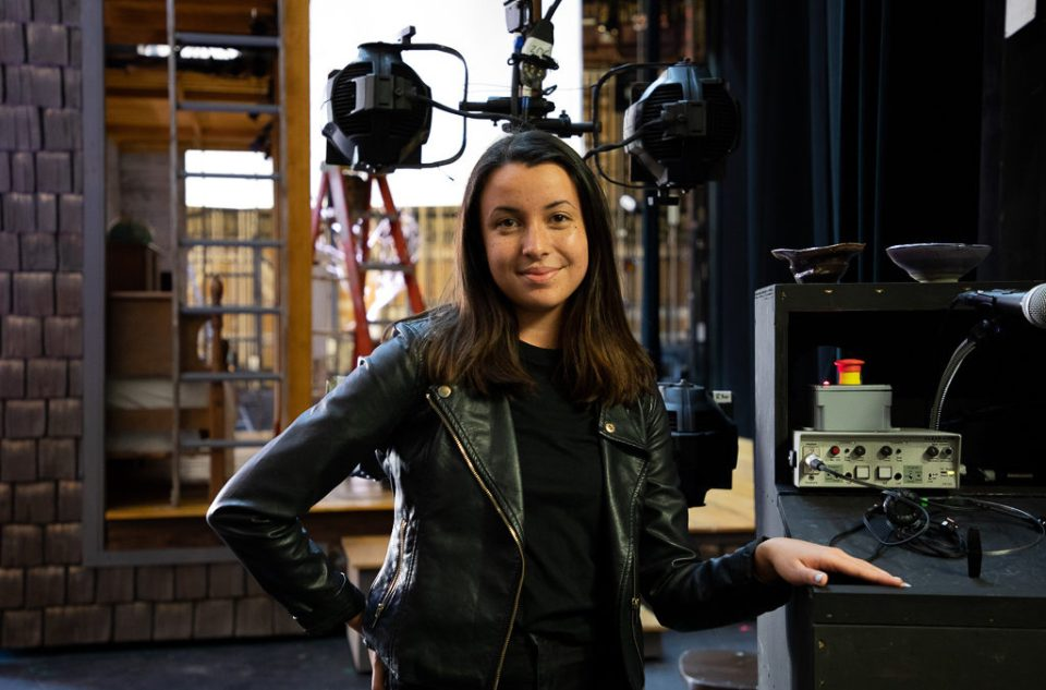 SDA Student Carrie Hiramatsu BFA '20 on set at The Cider House Rules. She is standing in front of a movie set, smiling and looking into the camera.