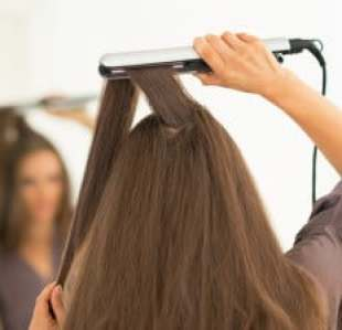 woman using a hair straightening iron